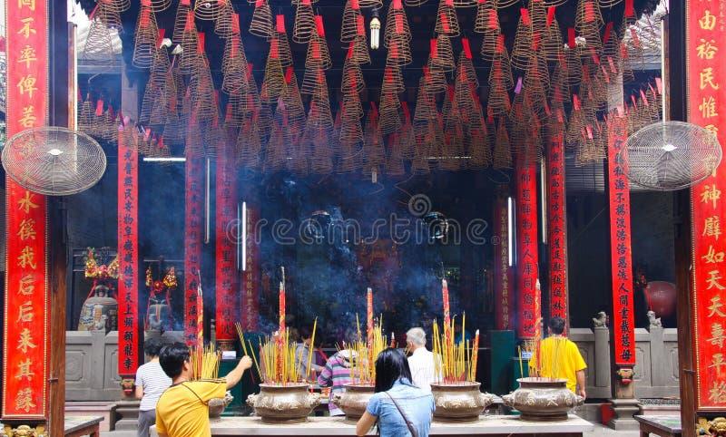 HO CHI MINH, VIETNAM - 5 GENNAIO 2015: Tempio buddista interno con l'attaccatura le bobine a spirale di incenso e dei bastoni bru immagini stock