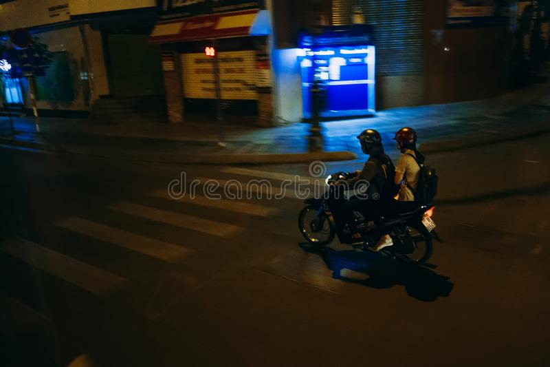 HO CHI MINH, VIETNAME - CERCA DO MARÇO DE 2017: Homem e mulher que montam um velomotor na noite fotografia de stock