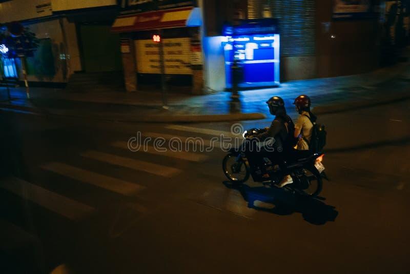 HO CHI MINH, WIETNAM - OKOŁO MARZEC, 2017: Mężczyzna i kobieta jedzie motocykl przy nocą fotografia stock