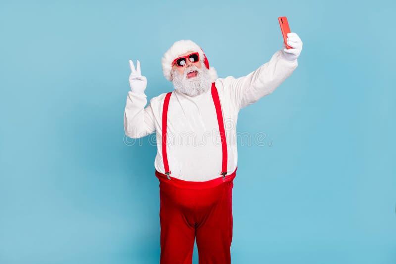 Ho-ho-ho Portret van overgewicht grappige hipster santa claus blogger in dop die zichzelf op de mobiele telefoon aanspreekt v royalty-vrije stock fotografie