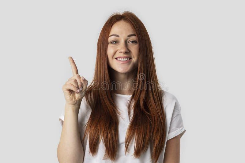 Ho un'idea! La bella donna della testarossa che tiene il dito ha indicato verso l'alto, mostrando qualcosa sopra la sua testa, fa immagini stock