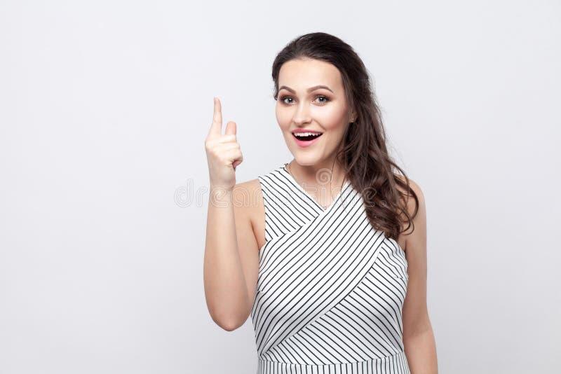Ho un'idea Ritratto di bella giovane donna castana stupita con trucco e la condizione a strisce del vestito e l'esame della macch fotografia stock