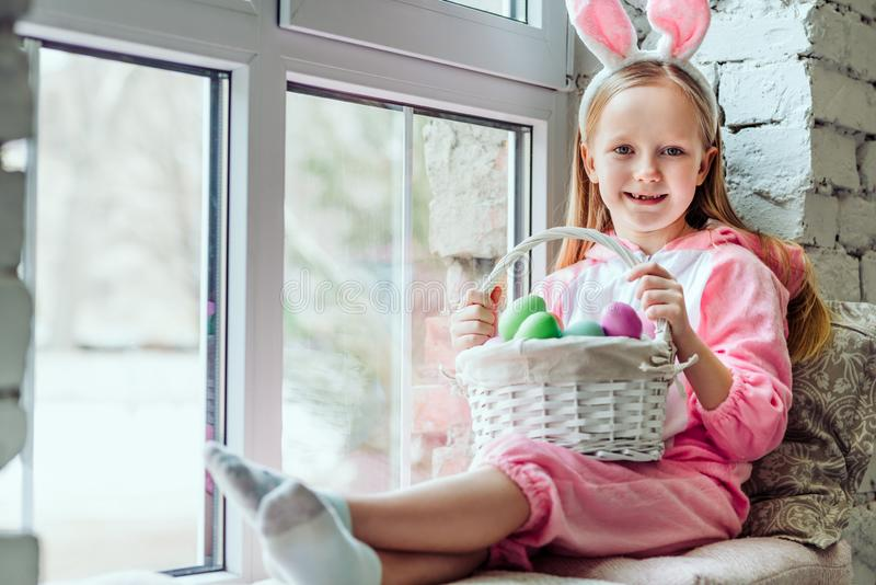 Ho un umore di pasqua La bella bambina in un costume del coniglio sta sedendosi a casa sul davanzale e sta tenendo un canestro di immagine stock libera da diritti