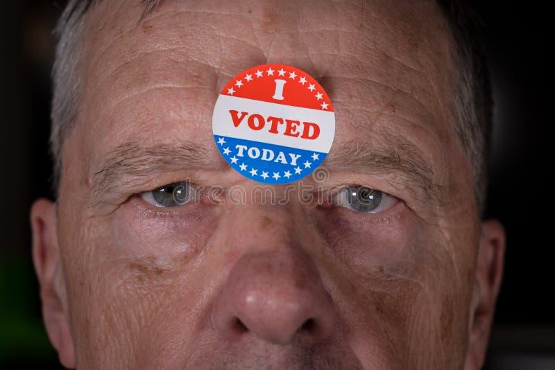 Ho votato oggi l'autoadesivo di carta sopra equipaggio la fronte con lo sguardo fisso arrabbiato alla macchina fotografica immagini stock libere da diritti