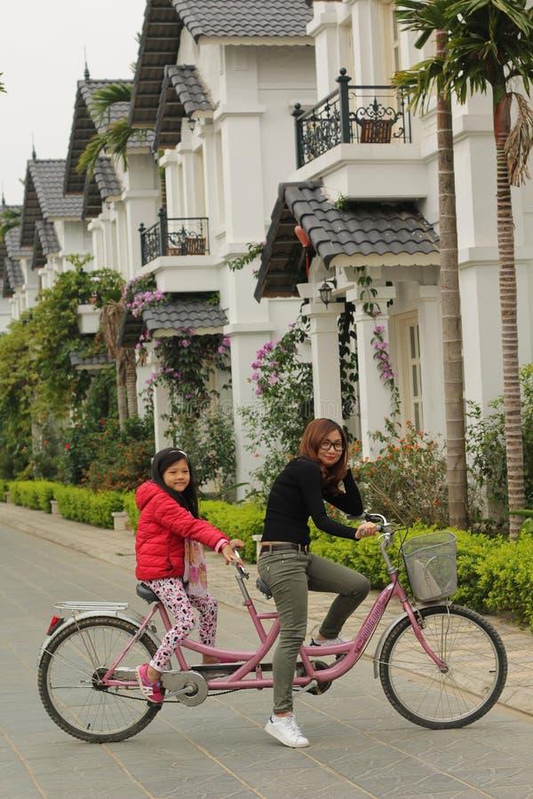 Hoa Binh, Vietname - dezembro 03,2016: A m?e e a filha est?o competindo a bicicleta na estrada imagem de stock royalty free