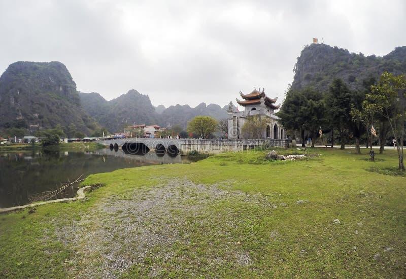 Hoalu Tempel, brug, meer en ingangspoort, door kalksteen wordt omringd - Ninh Binh Province, Vietnam dat stock afbeelding
