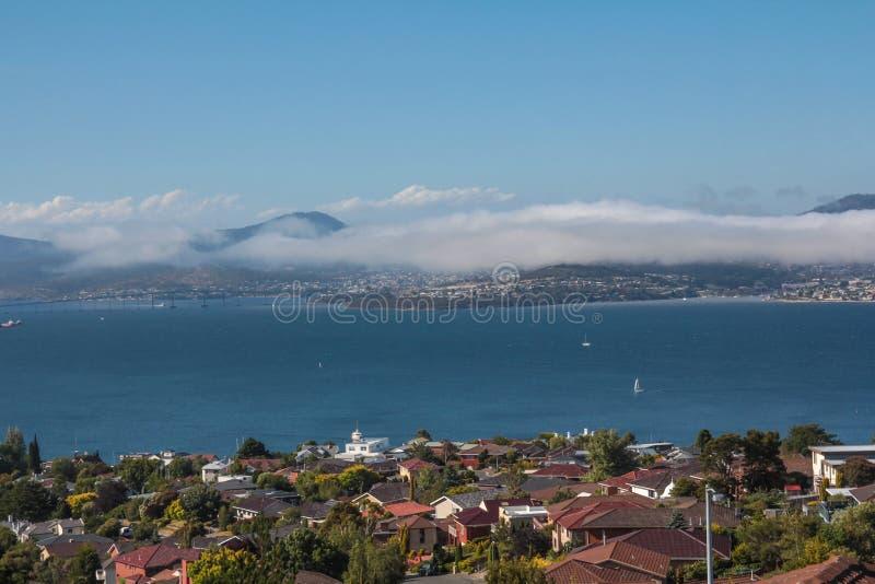 Hobart stad och derwent flod som beskådas från förort av den sandiga fjärden med havsmist arkivfoto