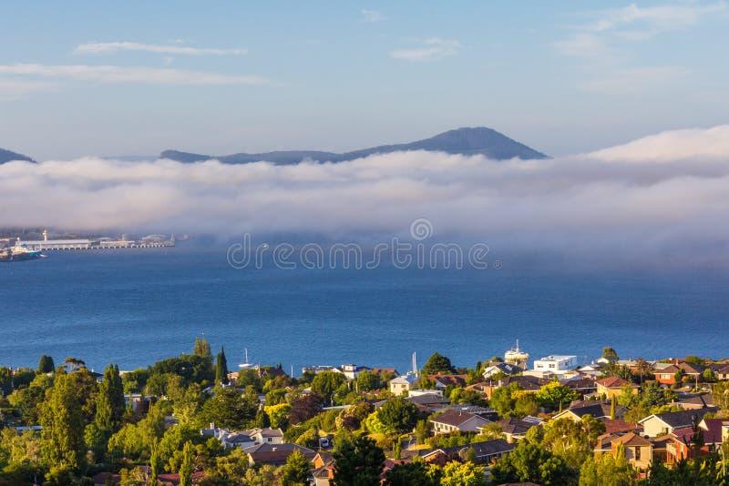 Hobart stad och derwent flod som beskådas från förort av den sandiga fjärden med havsmistrullning över östlig kust arkivfoton