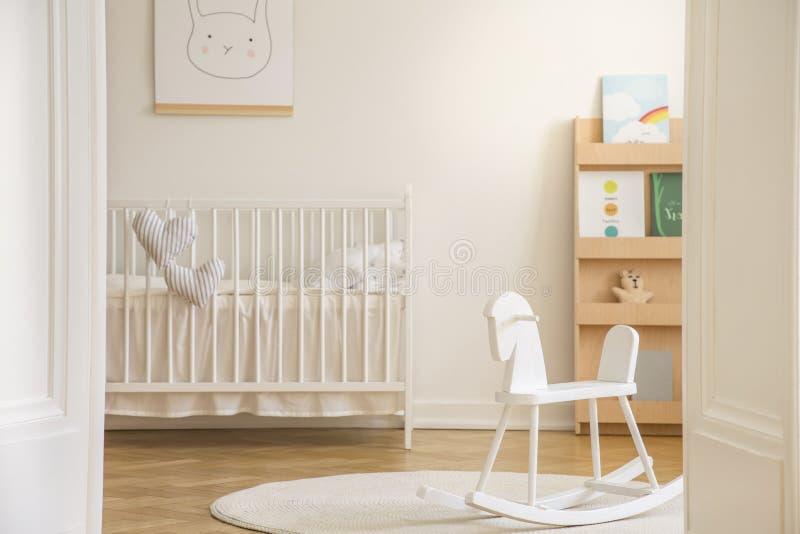 Hobbelpaard op deken in het witte binnenland van de jong geitje` s slaapkamer met konijnaffiche boven wieg stock foto's
