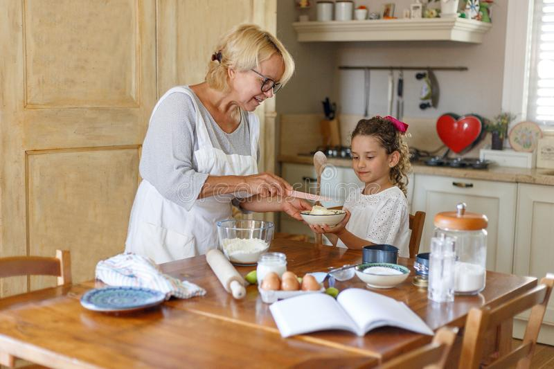 Cute little girl and her grandmother cooking in the kitchen together. royalty free stock images