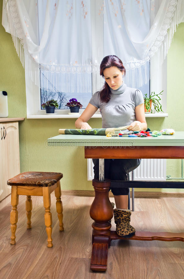 Hobby. The woman of middle age is engaged in embroidery royalty free stock image