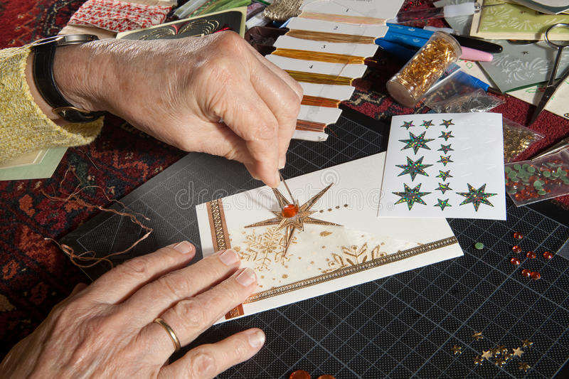 Hobby christmas cards. Hands of a woman crafting and scrap-booking christmas cards royalty free stock photos