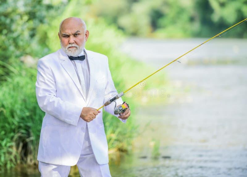 Hobby en recreatie Vissers in formeel kostuum Succesvolle vangst Bedrijfs succes De rijpe Visserij van de Mens de visser viert stock afbeelding
