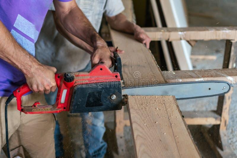 Hobby houten concept Bebouwde het profiel zijaanzicht foto van schrijnwerker handcraft met de houten raad van de partnerzaag om m stock foto