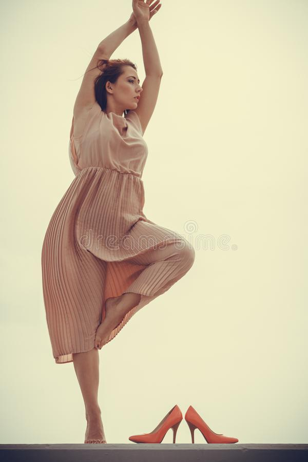 Woman dancing wearing long light pink dress royalty free stock photography