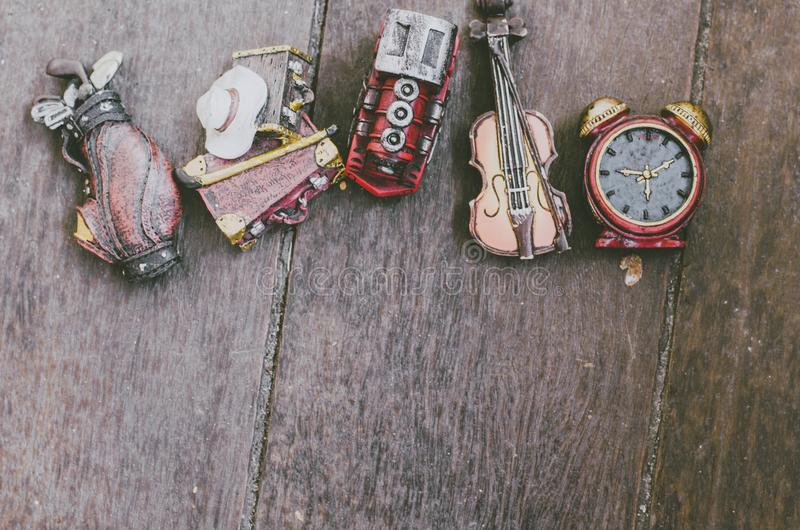 Leisure object concept image, miniature violin, clocks,travel bag and train on wooden floor. Hobby and leisure object concept image, miniature violin, clocks royalty free stock photography
