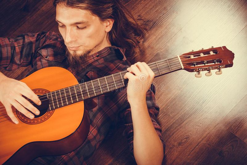 Man is playing the guitar. Hobby, music concept. Man is playing the guitar. Male is lying on the floor with his instrument stock photography