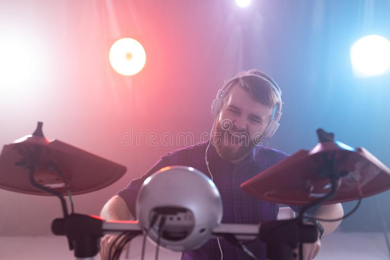 Hobby, music and people concept - portrait of a man with white headphones playing drums, having fun royalty free stock photography