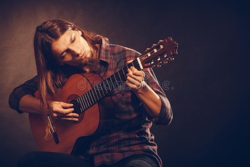 Guitarist is playing the guitar. Hobby passion concept. Guitarist is playing the guitar. Long haired performer and his instrument stock photo