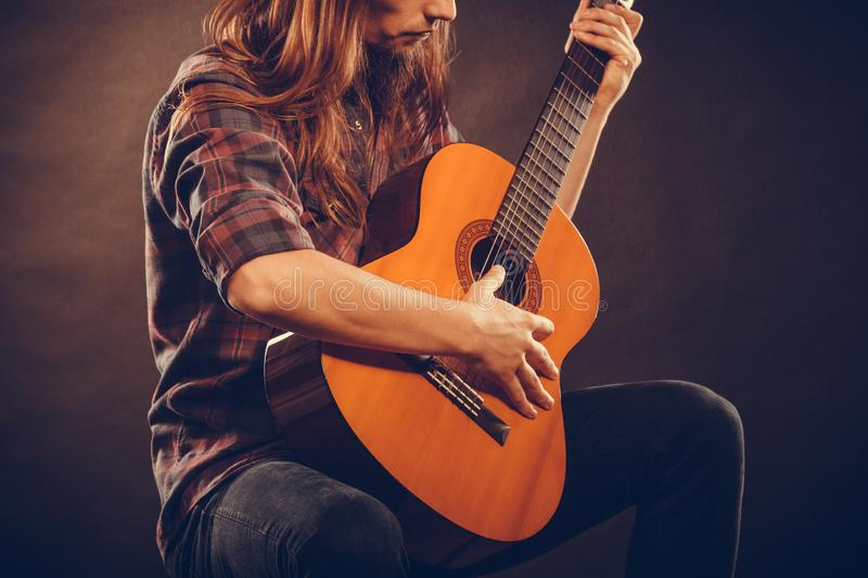 Guitarist is playing the guitar. Hobby passion concept. Guitarist is playing the guitar. Long haired performer and his instrument royalty free stock photo