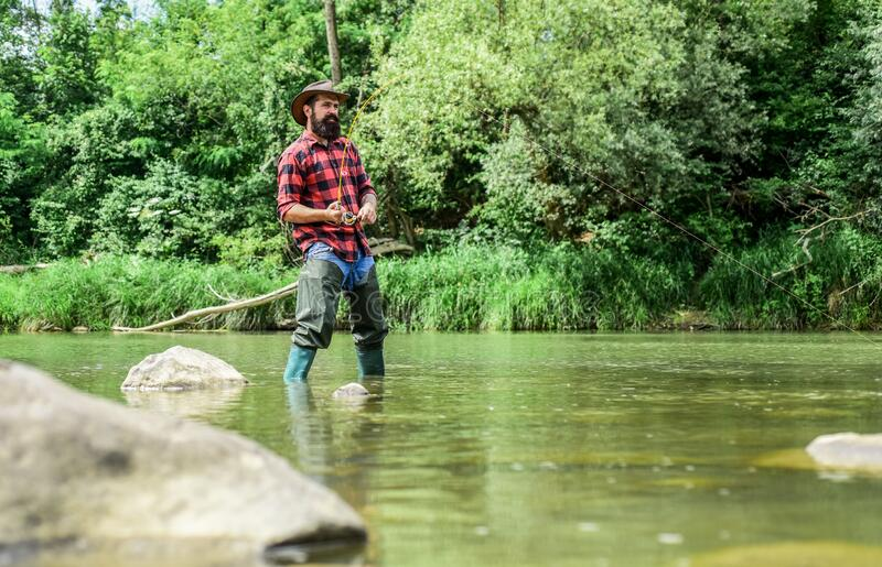 Hobby sport activity. Fish farming pisciculture raising fish commercially. River lake lagoon pond. Trout farm. Fisherman. Alone stand in river water. Man royalty free stock photography