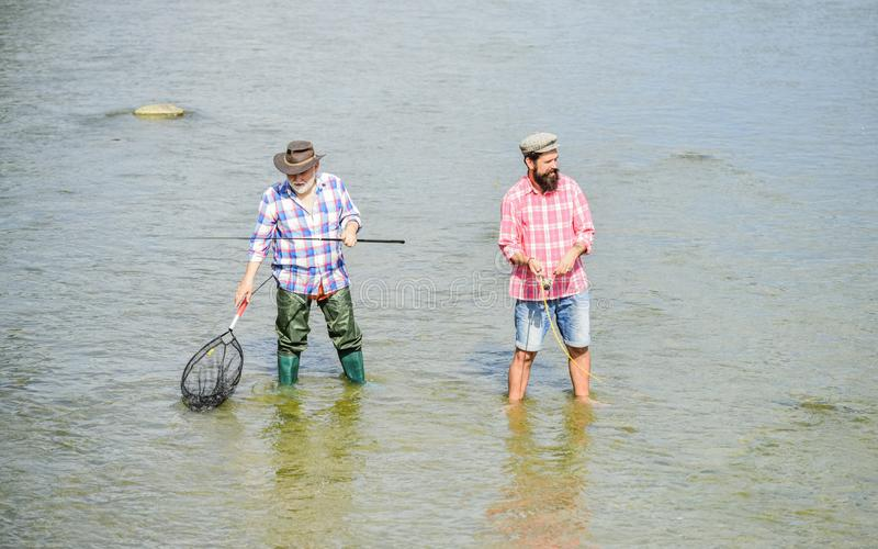 Hobby and sport activity. Fishing together. Teach man to fish and you feed him for lifetime. Male friendship. Father and. Son fishing. Summer weekend. Happy royalty free stock photography