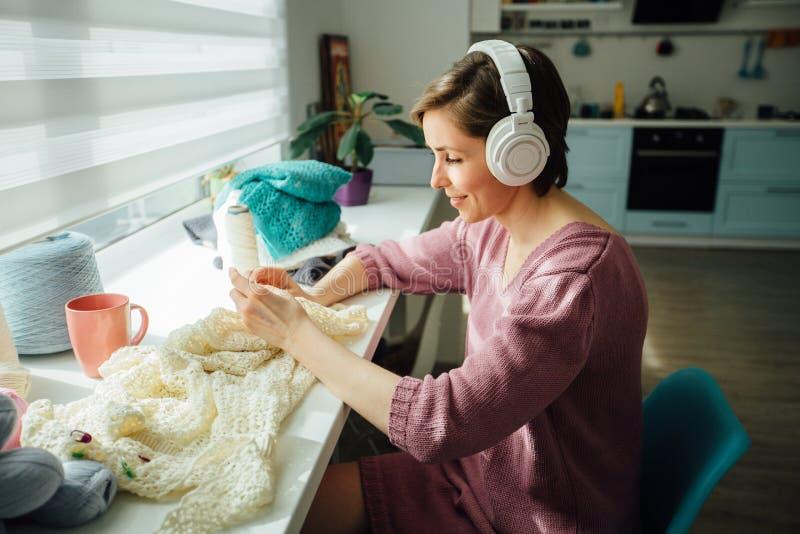 Hobby, stemmings en vrije tijdsconcept Vrouw het ontspannen met hoofdtelefoons terwijl de breiende tedere kleding met in zonnige  royalty-vrije stock fotografie