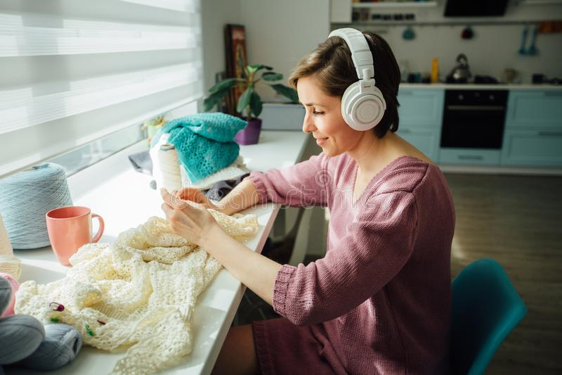 Hobby-, Stimmungs- und Freizeitkonzept Frau, die mit Kopfhörern beim Stricken des zarten Kleides mit Häkelarbeit am sonnigen Tag  lizenzfreie stockfotografie