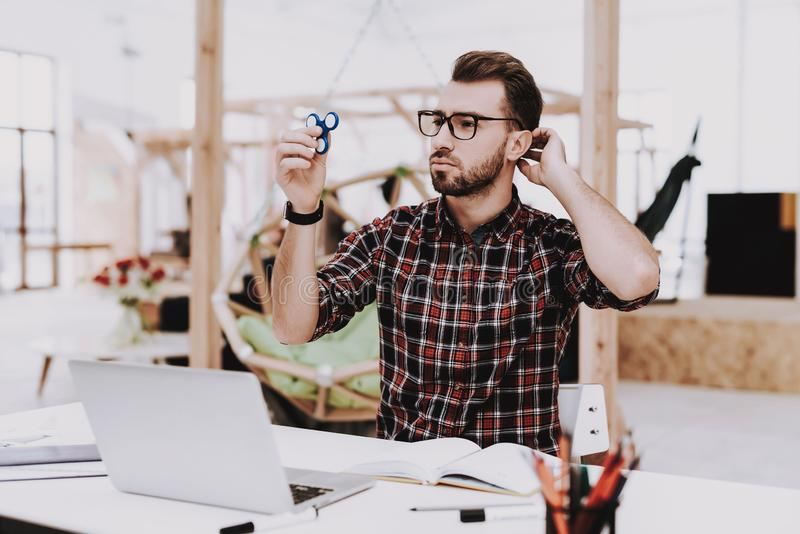 Hobby. Young Guy. Businessman. Spinning a Spinner royalty free stock image