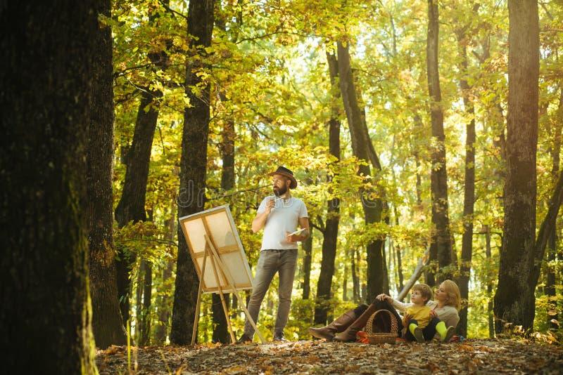 Hobbyconcept Het schilderen in aard Begin nieuw beeld Schoonheid van aard Gebaarde man vrouw en de leuke zoons ontspannende herfs stock afbeelding