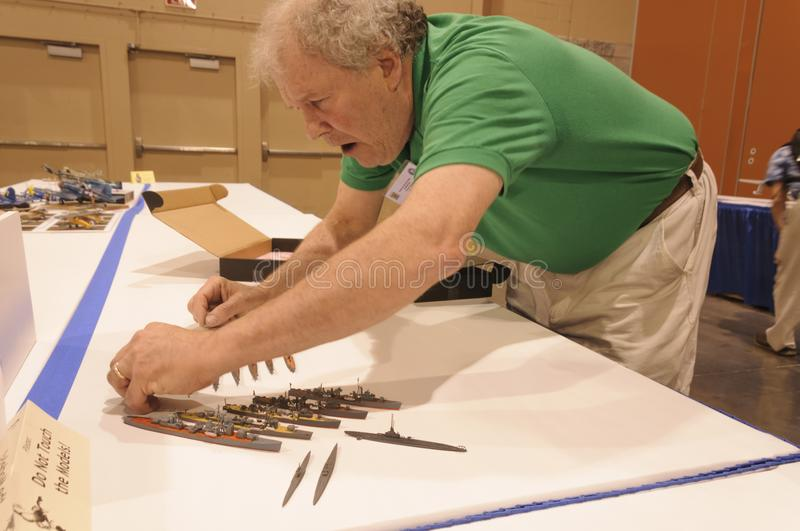 Man next to his display of nautical vessel models at the Modeling Convention in Phoenix, Arizona. Hobbyist and craftsman is a Participant at International stock images