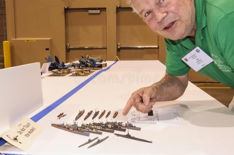 Hobbyist displays his models at the Modeling Convention in Phoenix, Arizona. Male Hobbyist of miniature ship models displays his nautical vessel models at the stock photography