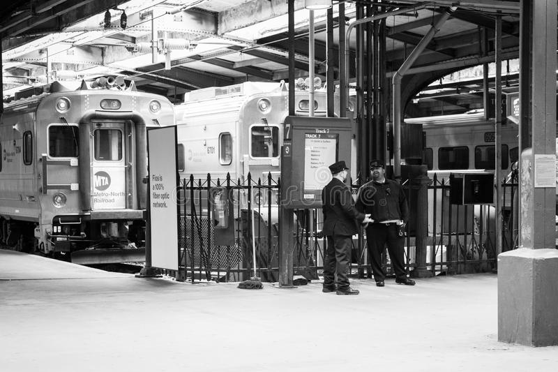 Hoboken Terminal Conductors. APRIL 11, 2016 - Hoboken, NJ: Railroad conductors stand by the tracks at Hoboken Terminal royalty free stock photo