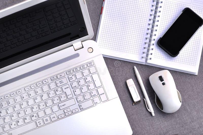 Hoch über Ansicht des Büroarbeitsplatzes mit naher hoher Computertastatur und -maus des Handys und des Laptops mit Notizbuch, Sti lizenzfreie stockbilder