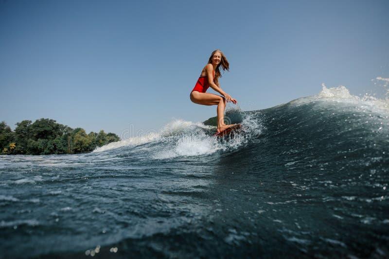 Hoch blaue Welle auf einem Vordergrund und jungen einem Blondine wakesurfin stockbild