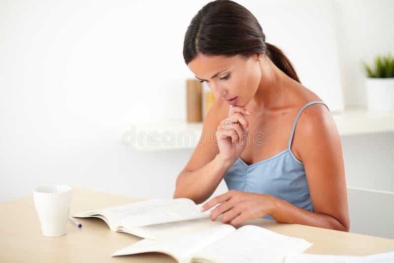 Hoch entwickelte denkende Frau beim Ablesen eines Buches stockfotografie