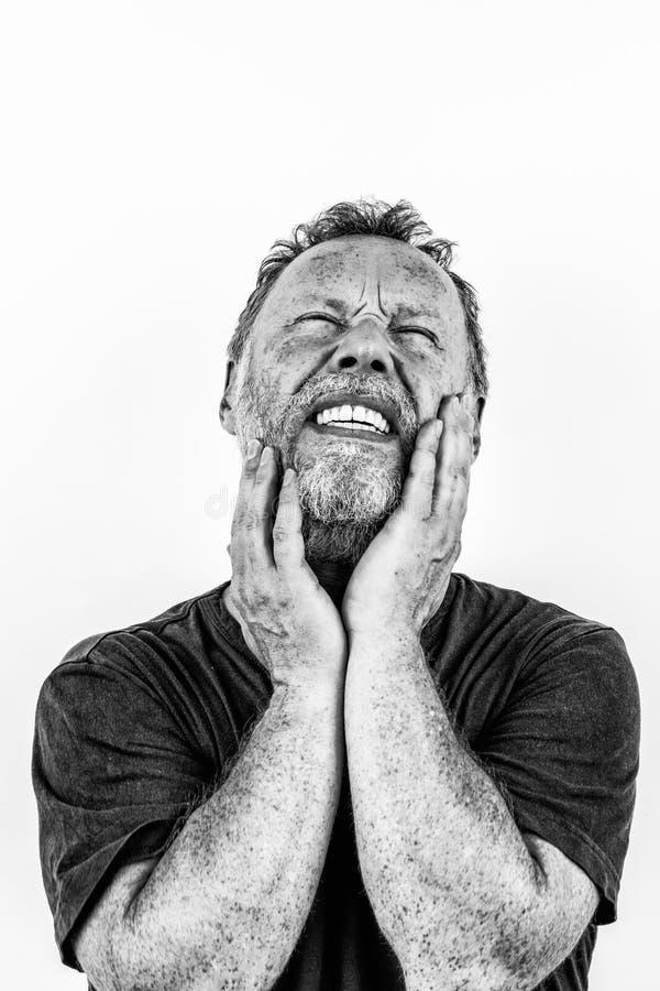 Hochauflösendes Schwarzweiss-Porträt eines Mannes mit Bart in den Schmerz stockfotografie