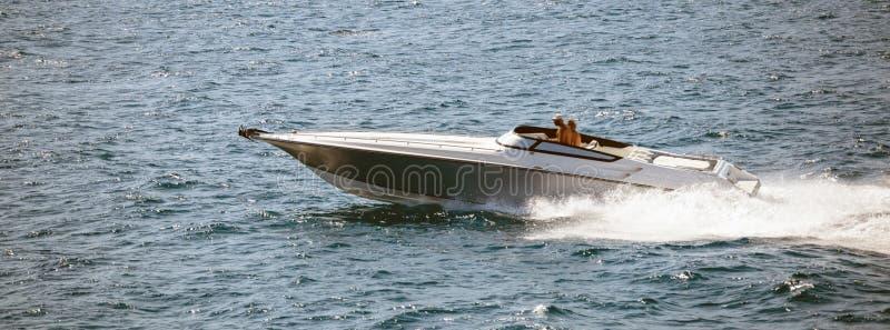 Hochgeschwindigkeitsboot geht schnell in ruhigen See Leute genießen den Sommersport Panoramablick, Fahne stockfotos