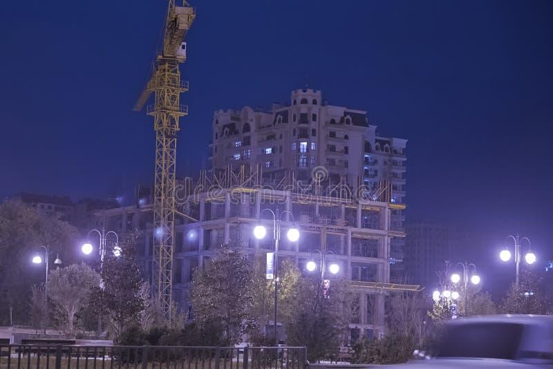 Hochhäuser im Bau mit Kränen am Abend Beleuchtungshochhäuser im Bau und Kräne an nah stockbild