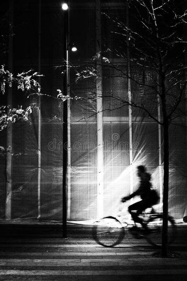 Hochkontrastbild der Silhouette des Fahrradfahrens in Bewegungsunschärfe im städtischen Umfeld lizenzfreie stockfotos