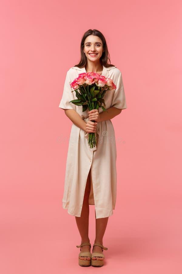 Hochlängliches vertikales Portrait attraktiv, schöne junge Frau, die schöne Blumen bekommt, mit einem Bouquet, das Spaß macht lizenzfreie stockfotografie