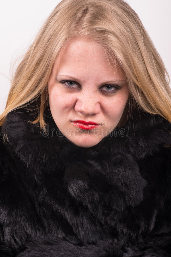 Hochnäsige verärgerte junge nette junge Frau in der Pelzjacke stockfotos