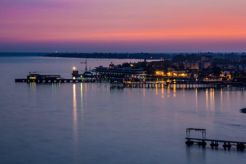 Hochroter Abendsonnenuntergang über Schwarzem Meer Sukhum, Abchasien Schattenbild des kauernden Geschäftsmannes stockfoto