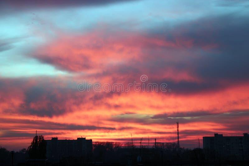 Hochroter Sonnenuntergang über mehrstöckigem Haus Abendstadtbild stockfoto