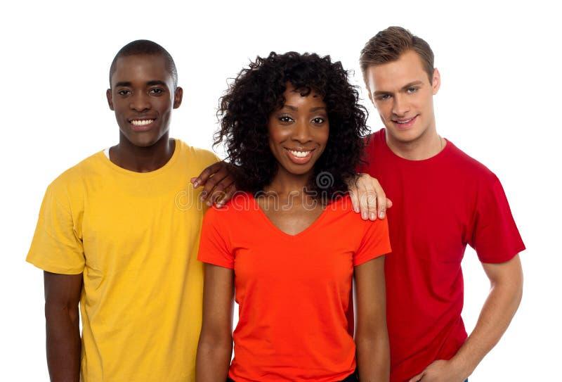 Hochschulfreunde, die in den casuals aufwerfen. Freundliche Gruppe lizenzfreie stockbilder