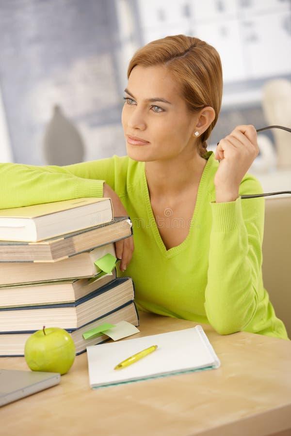 Hochschulmädchen, das mit Büchern lächelt lizenzfreie stockbilder