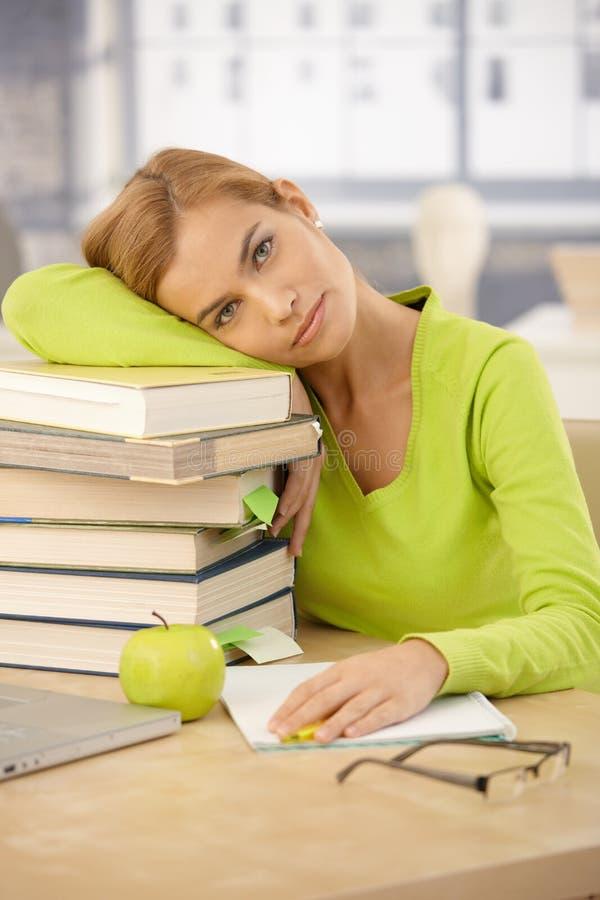 Hochschulmädchen, das mit Kopf auf Büchern sich entspannt lizenzfreie stockbilder