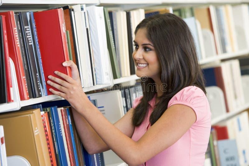 Hochschulstudent, der Buch von der Bibliothek auswählt stockbild
