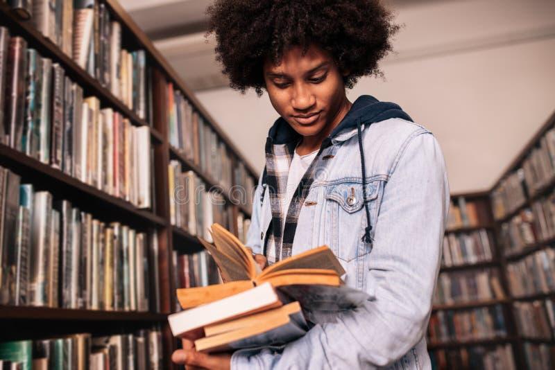 Hochschulstudent, der in der Bibliothek mit vielen Büchern steht stockfotografie