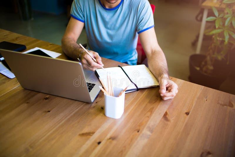 Hochschulstudent, der online unter Verwendung des netbook, bereitend zur Prüfung lernt vor Freiberuflerarbeitsabstand stockfoto